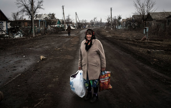 Eastern Ukrainian woman, one of over 1 million internally displaced persons due to conflict, has just returned from her destroyed home holding all her possessions, on main street in Nikishino Village, March 1, 2015 (© UNHCR/Andrew McConnell)