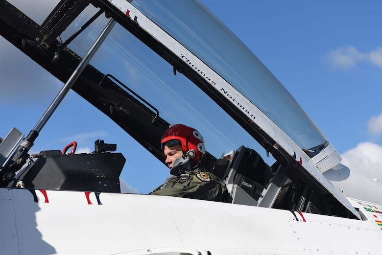 A man in a green flight suit and a red helmet sits in a white aircraft with the glass top propped up.