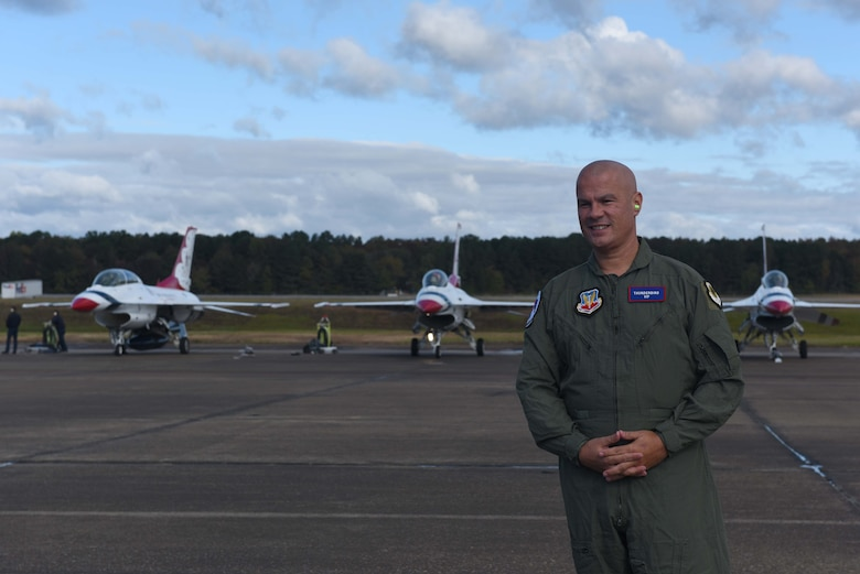 A man in a green flight suit stands before three white aircraft on a flightline.