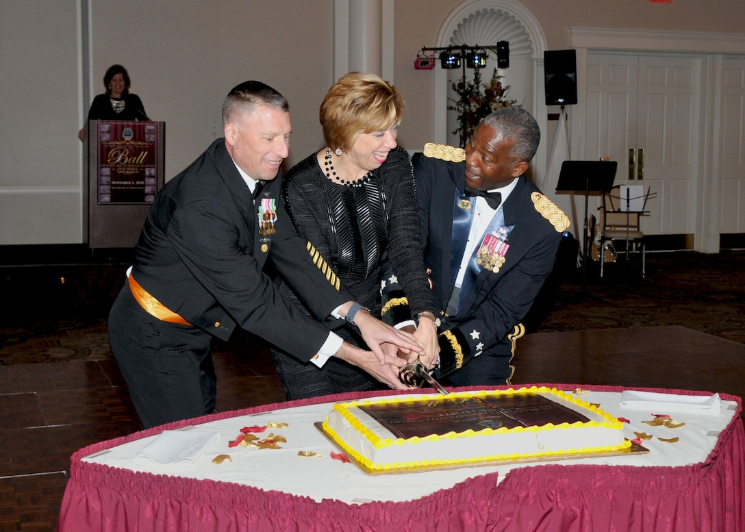 Left to right, Senior Enlisted Leader Navy Command Master Chief Shaun Brahmsteadt,  Under Secretary of Defense for Acquisition and Sustainment Ellen Lord and DLA Director Army Lt. Gen. Darrell Williams cut the cake with a ceremonial sword as DLA Chief of Staff Kristin French, officiates from lectern in background.