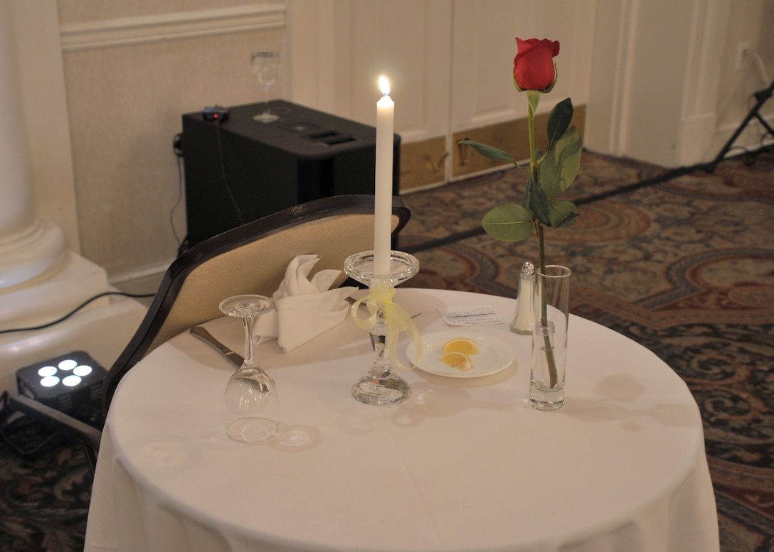 A chair is tipped up against a round table with white tablecloth, candle, single rose in a vase, an inverted glass and wedge of lemon on a plate. All symbolize the missing military and civilian members who cannot be present at the festivities.