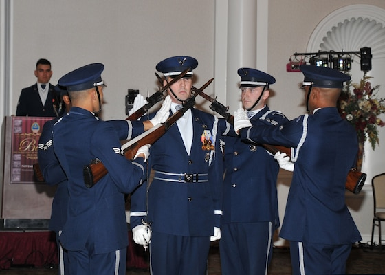 Five members of the Air Force Honor Guard Drill Team hold weapons at the ready to perform precision drill exercises to entertain the audience during the 2nd Annual DLA Ball.