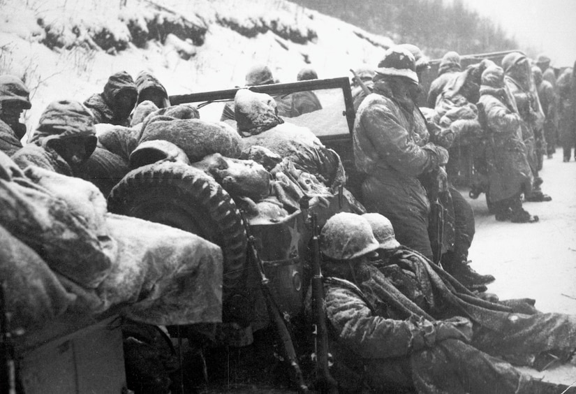 Astonished Marines of 5th and 7th Regiments, who hurled back surprise onslaught by three Chinese communist divisions, hear that they are to withdraw, circa December 1950 (U.S. Marine Corps/U.S. National Archives and Records Administration/Frank C. Kerr)