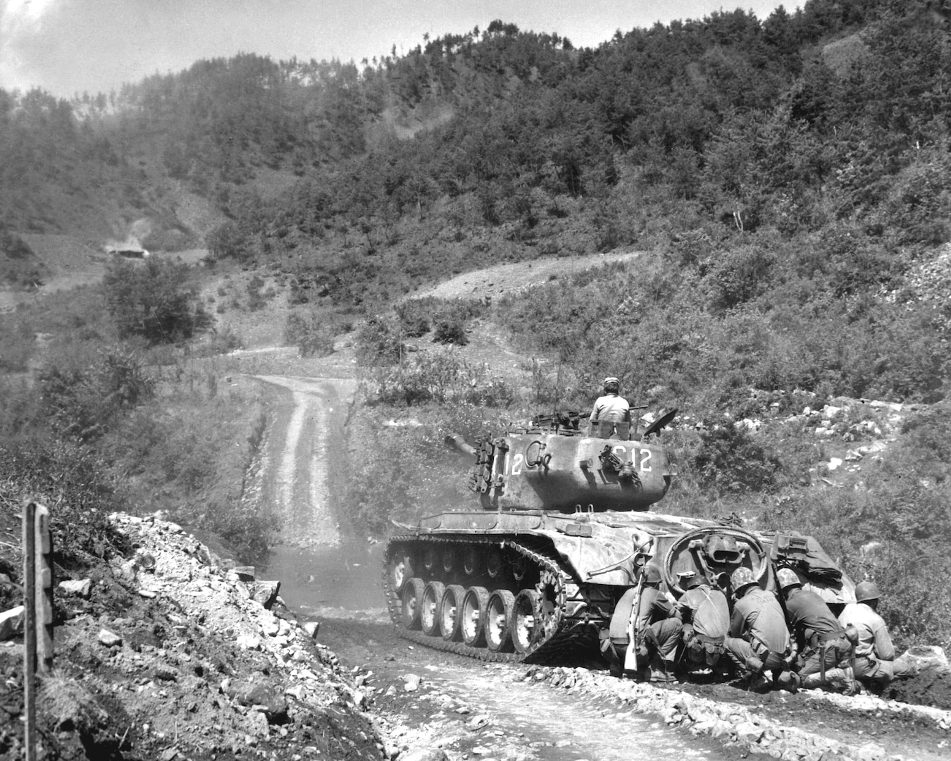 Marine infantrymen take cover behind tank while it fires on communist troops ahead, Hongchon Area, May 22, 1951 (U.S. Marine Corps/John Babyak, Jr.)