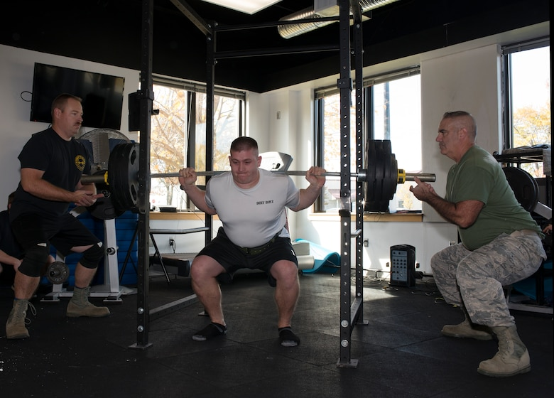 Tech Sgt. Aaron Marcaeu, an aircraft maintenance craftsman with the 157th Maintenance Group, squats more than 300 pounds during the first weight lifting competition held at Pease Air National Guard Base, N.H. Nov. 4, 2018. Master Sgt. Robert Guyer, the non-commissioned officer in charge with the 157th MXG, and Tech. Sgt. Todd Scruton, a crew chief with the 157th MXG, spot during the squatting portion of the weight lift challenge. (Photo by Airman 1st Class Victoria Nelson, 157th ARW Public Affairs)