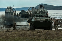 Marines and Sailors offload light armored vehicles from a landing craft air cushion on Alvund Beach, Norway during an amphibious landing in support of Trident Juncture 18, Oct. 30, 2018.