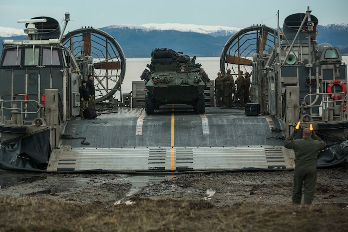 U.S. Marines and Sailors offload a light armored vehicle from a landing craft, air cushion on Alvund Beach, Norway, during an amphibious landing in support of Trident Juncture 2018, Oct. 30,