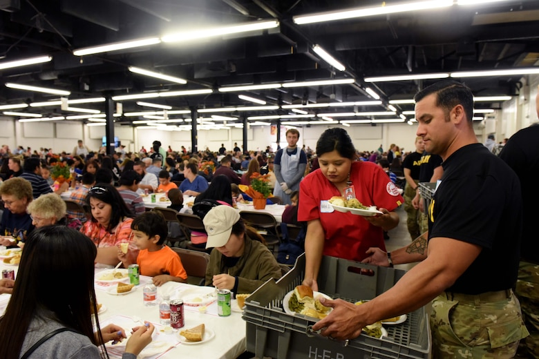 Sgt. 1st Class Jonathon Murphy, 344th Military Intelligence Battalion instructor, delivers food during the Feast of Sharing at the Wells Fargo Pavilion in San Angelo, Texas, Nov. 4, 2018. The Feast of Sharing is an event that provides a Thanksgiving meal, music and kid-friendly activities to families in Texas. (U.S. Air Force photo by Senior Airman Randall Moose/Released)