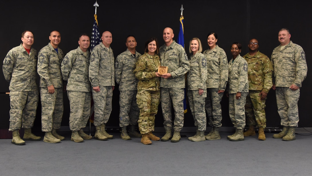 U.S. Air Force Chief Master Sgt. JoAnne Bass, 2nd Air Force command chief, is joined by Keesler chief master sergeants to present Chief Master Sgt. Kenneth Carter, 81st Training Wing command chief, with a momento during his retirement farewell reception at Keesler Air Force Base, Mississippi, Nov. 2, 2018. Carter retired with more than 29 years of military service. (U.S. Air Force photo by Kemberly Groue)