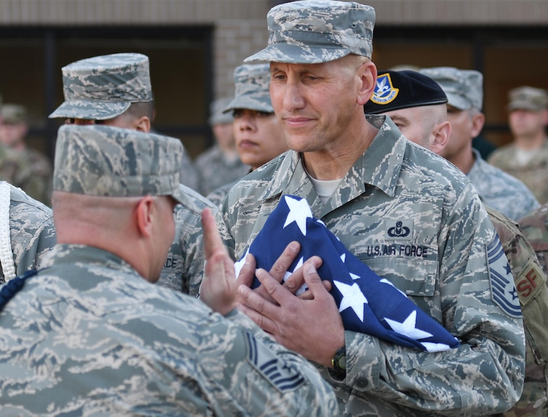 U.S. Air Force Senior Master Sgt. Andrew Bodine, 81st Training Group military training superintendent, presents Chief Master Sgt. Kenneth Carter, 81st Training Wing command chief, with the U.S. Flag during a retreat ceremony at Keesler Air Force Base, Mississippi, Nov. 2, 2018. The ceremony was held in honor of Carter who retired with more than 29 years of military service. (U.S. Air Force photo by Kemberly Groue)