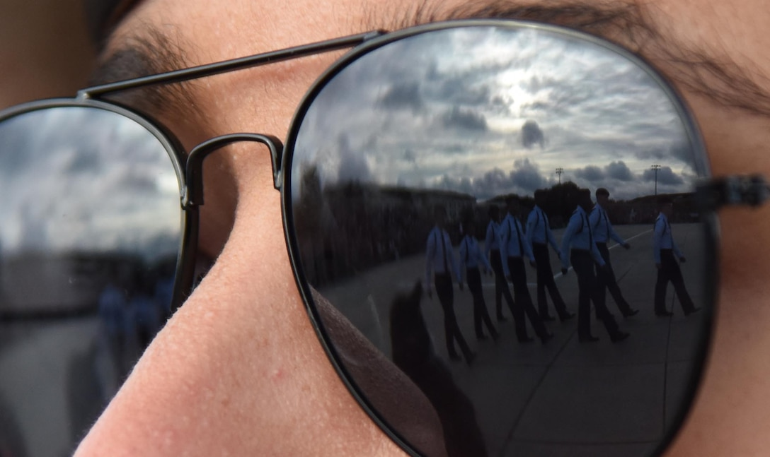Members of the 338th Training Squadron regulation drill team performance are seen through the sunglasses reflection of U.S. Air Force Airman Jayden Burns, 334th Training Squadron student, during the 81st Training Group drill down on the Levitow Training Support Facility drill pad at Keesler Air Force Base, Mississippi, Nov. 2, 2018. Airmen from the 81st TRG competed in a quarterly open ranks inspection, regulation drill routine and freestyle drill routine. (U.S. Air Force photo by Kemberly Groue)