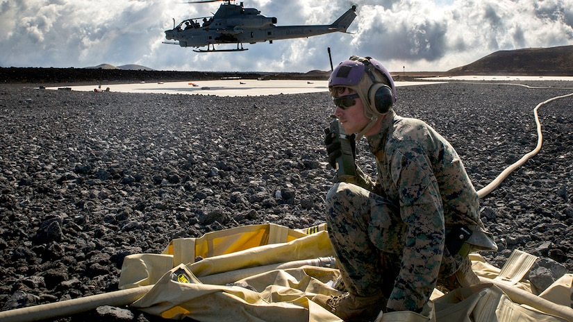 Marine controls forward arming and refueling point operations after refueling Bell AH-1W Super Cobra at Pohakuloa Training Area, Hawaii, July 18, 2018 (U.S. Marine Corps/Adam Montera)