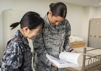 Japan Air Self-Defense Force Senior Airman Shimizu, left, a 37th Surveillance Squadron radar maintenance technician, looks at a Japanese phrase book with U.S. Air Force Airman 1st Class Hannah Tatum's, a 35th Communications Squadron radio frequency transmission systems technician, during a bilateral exchange program at Yamada Sub Base, Yamada Town, Japan, Oct. 17, 2018. U.S. Air Force members from various career fields stayed with their JASDF counterparts to better integrate with each other. Participants obtained a deeper understanding of cultural differences among themselves and learned to perform tasks together, ensuring fluid mission execution in the future. (U.S. Air Force photo by Senior Airman Sadie Colbert)