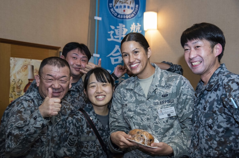 Japan Air Self-Defense Force members with the 37th Surveillance Squadron and a U.S. Air Force Airman 1st Class Hannah Tatum, a 35th Communications Squadron radio frequency transmissions systems technician, pause for a photo during a bilateral exchange program at Yamada Sub Base, Yamada Town, Japan, Oct. 17, 2018. During the exchange, personnel worked together and fellowshipped with one another to deepen bonds and better enhance mission execution through getting to know each other in and out of a work environment. (U.S. Air Force photo by Senior Airman Sadie Colbert)