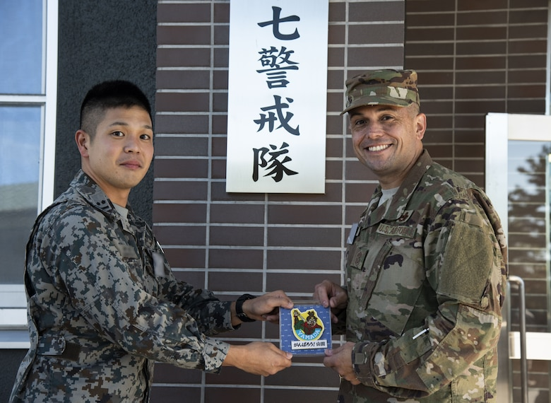 Japan Air Self-Defense Force 1st Lt. Kimamura, left, a 37th Surveillance Squadron weapons director, gives U.S. Air Force Chief Master Sgt. John Alsvig, right, the 35th Fighter Wing command chief, a gift during a bilateral exchange program at Yamada Sub Base, Yamada Town, Japan, Oct. 18, 2018. Alsvig stayed for the first two days of the exchange to learn about the 37th Surveillance Squadron's mission and how they work alongside their allies to maintain peace and balance in the Indo-Pacific region. (U.S. Air Force photo by Senior Airman Sadie Colbert)