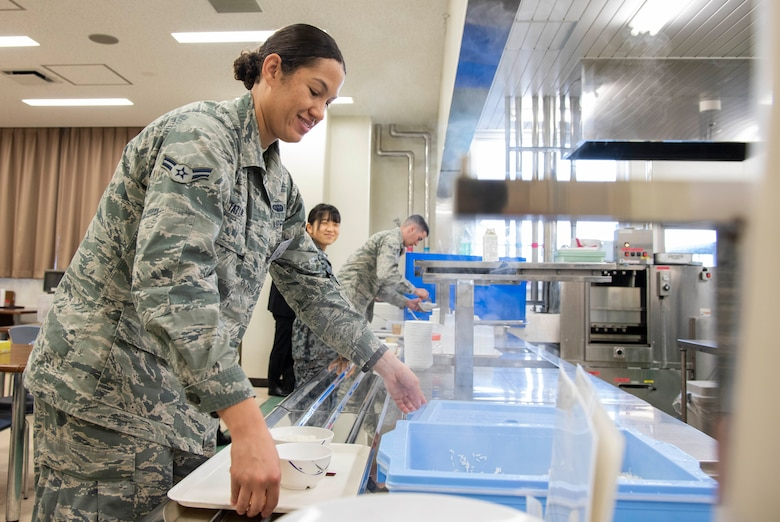 U.S. Air Force Airman 1st Class Hannah Tatum, a 35th Communications Squadron radio frequency transmission systems technician, grabs rice during a bilateral exchange program at Yamada Sub Base, Yamada Town, Japan, Oct. 18, 2018. During the event, U.S. Air Force service members stayed with Japan Air Self-Defense Force counterparts, learning to better integrate with each other and reinforce U.S. and Japan relations. (U.S. Air Force photo by Senior Airman Sadie Colbert)