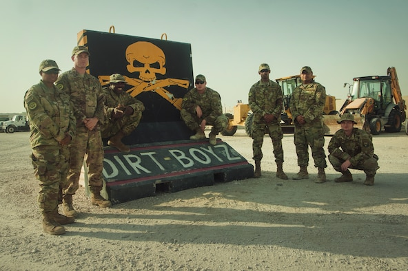 U.S. Air Force Airmen from the 379th Expeditionary Civil Engineer Squadron pavements and equipment shop, stand next to their unit mural Nov. 5, 2018, at Al Udeid Air Base, Qatar. Airmen from the flight conducted quick-turn repairs to the base flight line after it was damaged by a lightning storm Oct. 24. (U.S. Air Force photo by Tech. Sgt. Christopher Hubenthal)