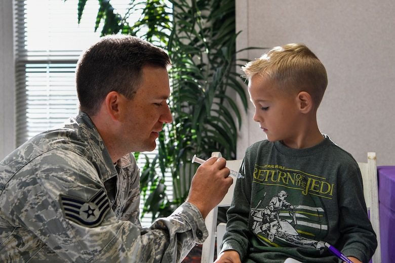 Staff Sgt. Robert Youmans, 628th Aerospace Medical Squadron NCO in charge of community health, gives a fake vaccination to a youth center member during a mock pre-deployment, Nov. 3, 2018, at Joint Base Charleston, S.C.