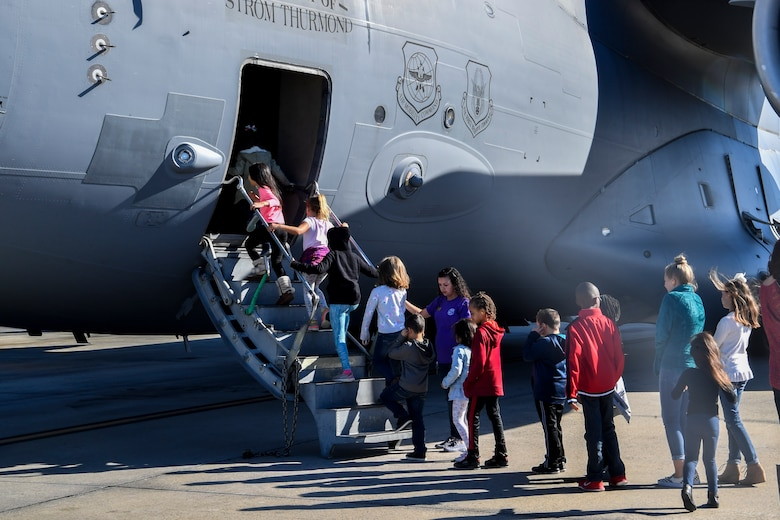 Kids climb on to a C-17 Globemaster III during a mock deployment, Nov. 3, 2018, at Joint Base Charleston, S.C.