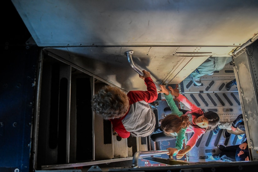 Kids climb into the cockpit of a C-17 Globemaster III during a mock deployment, Nov. 3, 2018, at Joint Base Charleston, S.C.