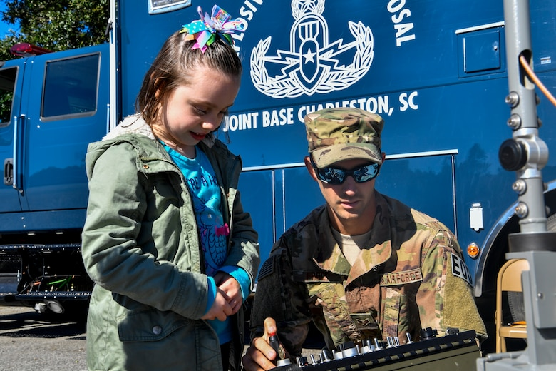 Senior Airman Michael Frook, 628th Civil Engineer Squadron explosive ordnance disposal technician, shows a youth center child how to control a robot during a mock deployment, Nov. 3, 2018, at Joint Base Charleston, S.C.