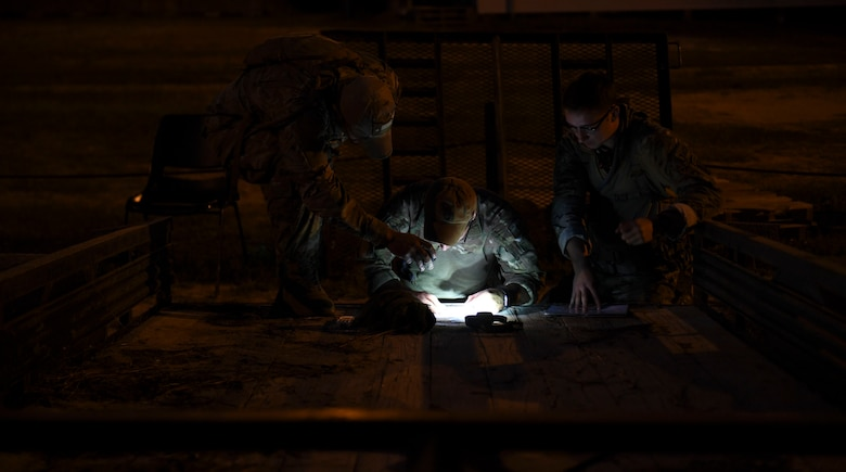 Competitors from the 20th Air Support Operations Squadron plan their route during the night land navigation event of Dragon Challenge 2018 at Fort Bragg, North Carolina Oct. 31, 2018. The event required competitors to navigate through the woods in the dark to as many points as possible within the allotted time. (U.S. Air Force photo by 1st Lt. Faith Brodkorb)