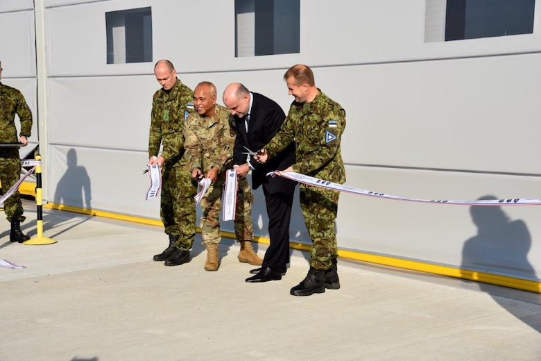 Four men stand in front of a building and cut a ribbon.