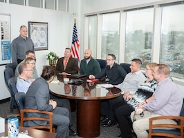 Eleven representatives sit around a table for a Technology Council meeting