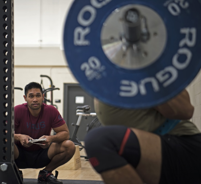 Clayton Bautista, Five Star Nutrition general manager, left, ensures Staff Sgt. Allen Plata, 20th Equipment Maintenance Squadron stockpile management crew chief, has proper form while power lifting at Shaw Air Force Base, S.C., Nov. 1, 2018.