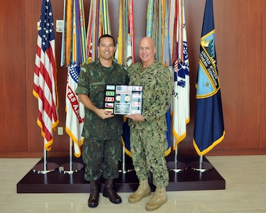 Brazilian Navy Cdr. Domingos Rodriguez Sousa, Partner Nation Liaison Officer (PNLO) assigned to U.S. Southern Command (SOUTHCOM) presents a plaque of appreciation to Adm. Kurt Tidd.