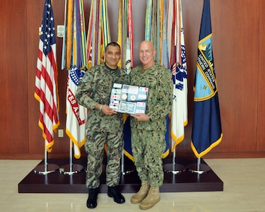 Peruvian Army Col. Walter Ocampo, Partner Nation Liaison Officer (PNLO) assigned to U.S. Southern Command (SOUTHCOM) presents a plaque of appreciation to Adm. Kurt Tidd
