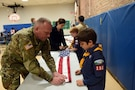 Sgt. David Lietz, public affairs sergeant with the 85th Support Command, shows a student how to fold an American Flag during the Lyon Elementary School Veteran's Day observance in Glenview, Illinois, November 5, 2018.