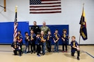 Sgt. David Lietz, public affairs sergeant with the 85th Support Command, pauses for a photo with Officer Joel Detloff, from the Glenview Police Department and students from Lyon Elementary School during the school's Veteran's Day observance in Glenview, Illinois, November 5, 2018.