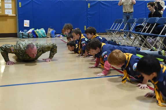Sgt. David Lietz, public affairs sergeant with the 85th Support Command, shows students how to conduct a push up during the Lyon Elementary School Veteran's Day observance in Glenview, Illinois, November 5, 2018.