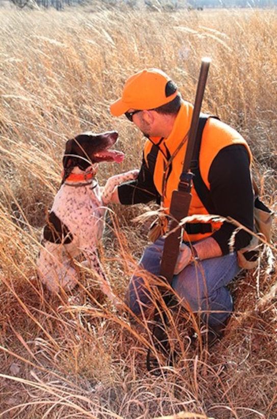 The Kansas City District urges all hunters to wear proper attire and be very conscious of their surroundings. Here a hunter works with a hunting dog.