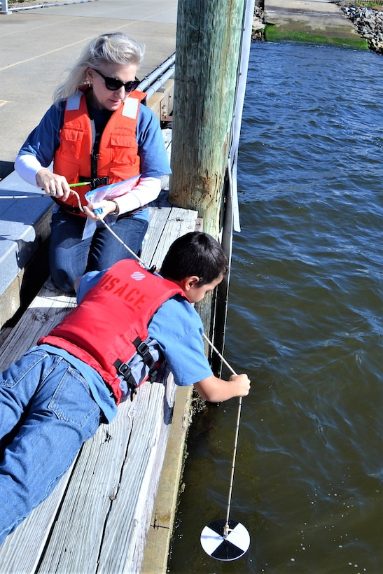 Fifth-grade boy for Norfolk Christian Schools is hanging a black and white disk from a rope off of a dock while his female teacher kneels beside him to help