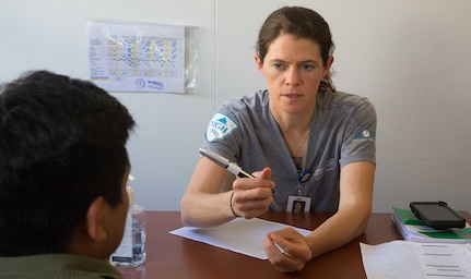 Lindsey Martin, a civilian nurse practitioner from Boston, and a member of the Global Disaster Response Team, Massachusetts General Hospital, discuss health concerns with a patient at one of two medical sites.