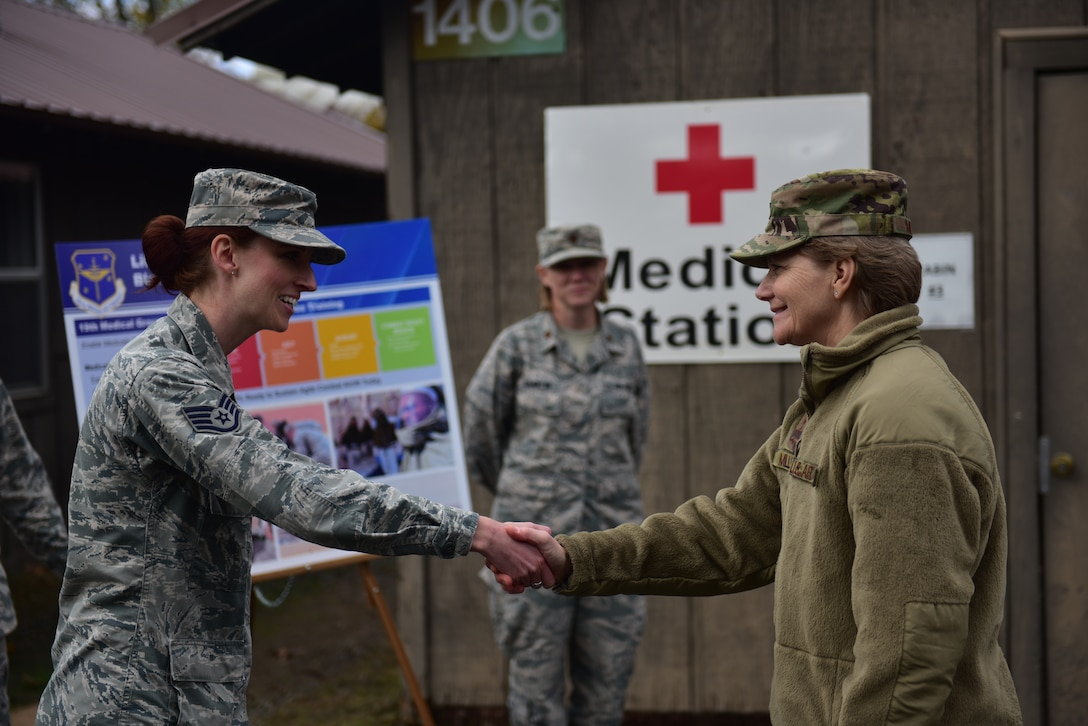 A woman in the operational camouflage patter uniform shakes hands with a woman wearing the airman battle uniform.