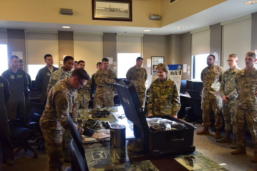 A room full of Airmen watch another Airmen mess with some equipment.