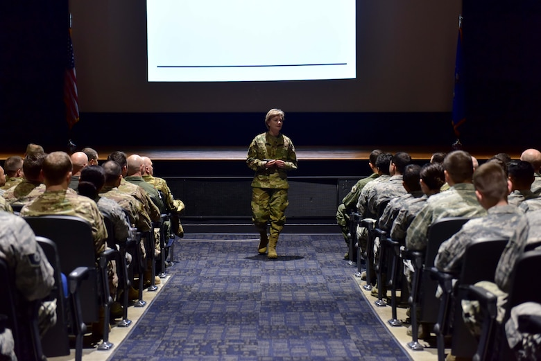 A woman wearing the operational camouflage pattern uniform speaks to a room full of Airmen.