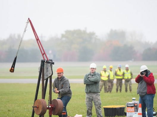 An Air Force Life Cycle Management Center's F-15 Engineering Branch team member pulls the trigger on their trebuchet-style catapult to hurl a small pumpkin during the 14th annual Wright-Patterson Air Force Base, Ohio, pumpkin chuck Nov. 2.