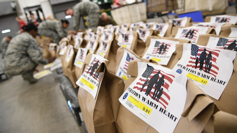 Hill's First Sergeant Council and the base commissary packaged 200 Operation Warm Heart Thanksgiving bags on Nov. 2, 2018, at Hill Air Force Base, Utah. The bags, filled with side dishes, along with a turkey and pie, donated by commissary vendors, will be deliver to Airmen to assist with the upcoming holiday. (U.S. Air Force photo by R. Nial Bradshaw)