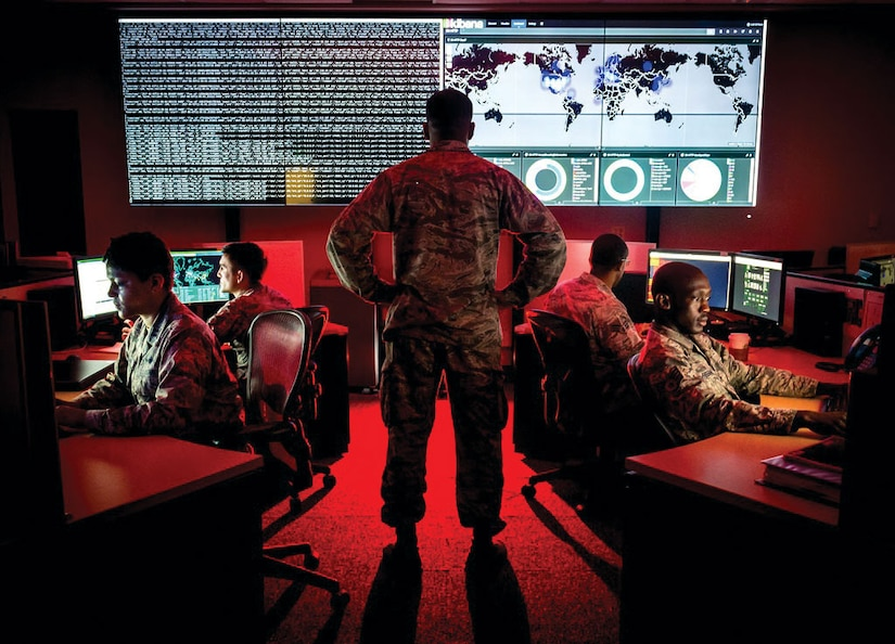 A cyber warfare operations officer reviews visualization data as analysts review log files and provide a cyber threat update.