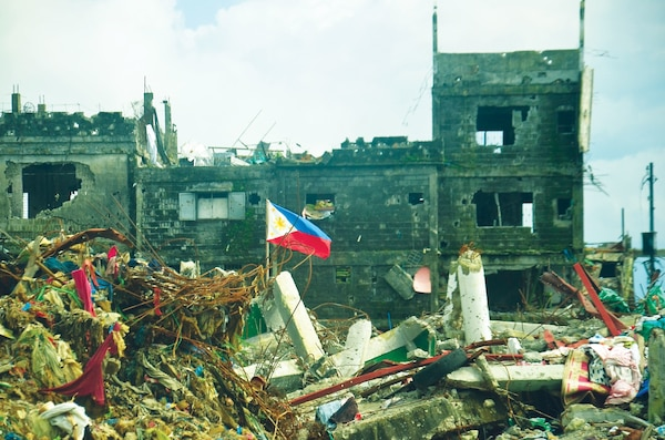 Philippine flag flown in war torn Marawi. Published in PRISM w/ permission from iStock. Photo ID: 899073932