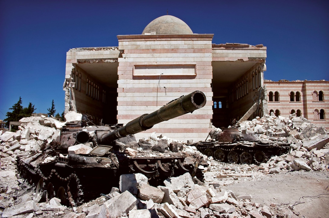 Two destroyed tanks in front of a mosque in Azaz, Syria. A battle between the Free Syrian Army (FSA) and the Syrian Arab Army (SAA) was fought from March to July in 2012 for control over the city of Azaz, north of Aleppo, during the Syrian civil war. (Christian Triebert) https://www.flickr.com/photos/christiaantriebert/7955551210/in/photolist-d81hd3-hHUUvN-hHTXzB-fatNA7-fk4mmb-fjPaNt-fk4nUL-fk4zjQ-fk4w7Y-fk4vD7-rjjjt6-fk4rvq-fk4wSo-fjPdRp-fjPm6H-pPYm2H-fk4pvu-AKQ15P-DNX2At-AJCGN9-DNX2mk-t411ip-xDKhtL-xF6mL8-xCa2E7-xnRYk3-xDD42j-xC9XqW-wHASdz-wHAHBr-xnRWxL-xnYrd8-xF5R6X-xnXTB2-xDCSH3-xF6kD8-xC9sAb-xnY4jZ-xF6gT2-xEt2cp-xnXYwc-xDCDdC-xnRJ9Y-xnXWQ6-xEtsmH-wHAt9D-xEtvnc-xDD2jS-xDD88f-xF69Xt/. Licensed under Creative Commons Attribution 2.0 Generic License. Photo unaltered.