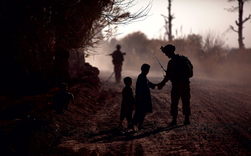 In 2011, a U.S. marine greets local children during a partnered security patrol with Afghan National Army soldiers in Helmand Province, Afghanistan. The marines aided Afghan National Security Forces in assuming security responsibilities; their interoperability is designed to further the expansion of stability, development, and legitimate governance by defeating insurgent forces and helping to secure the Afghan people. (DOD)