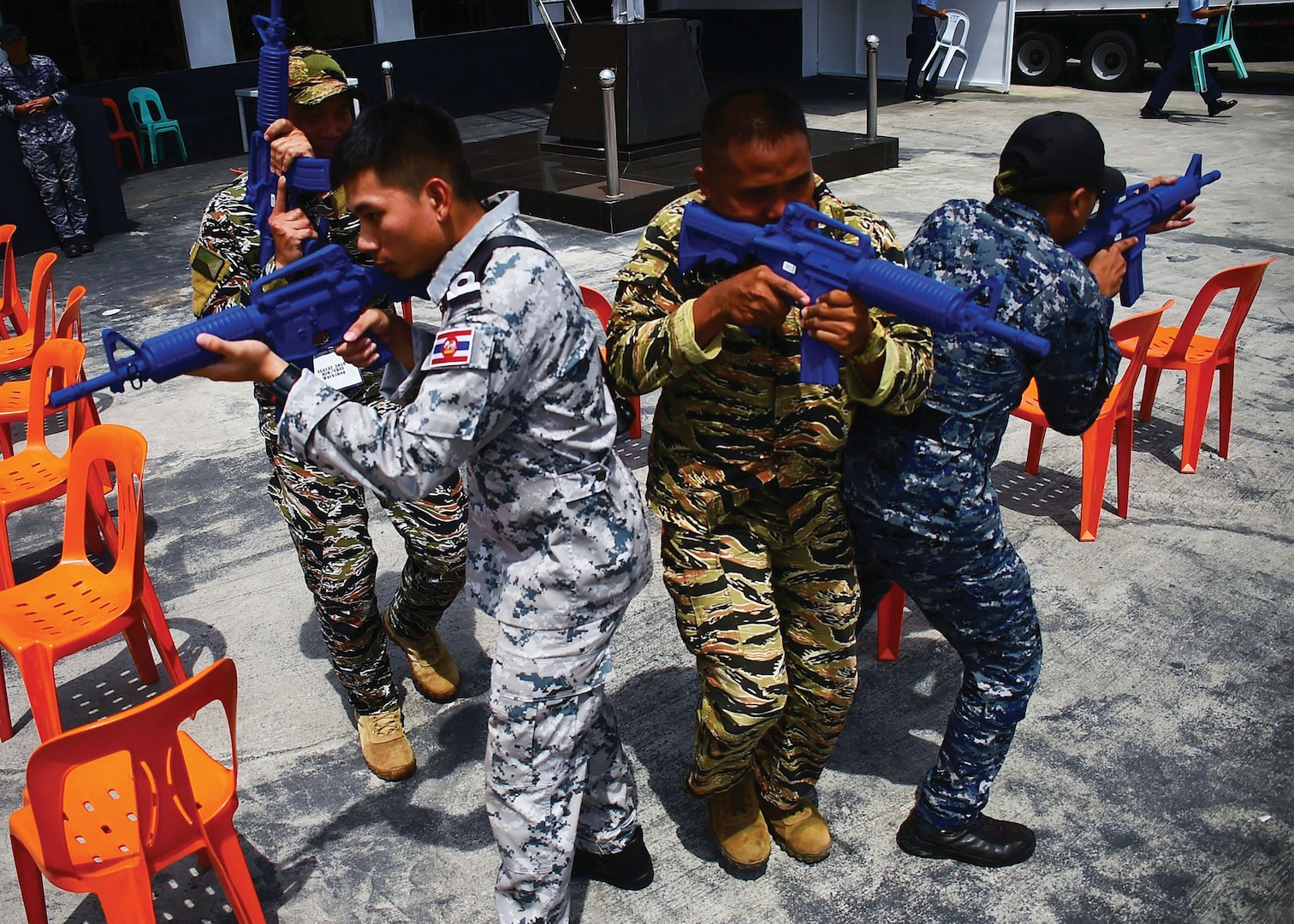 """In August, a Royal Thai Coast Guardsman (left), A Philippine sailor (center), and a Philippine Coast Guardsman practice tactical visit, search, and seizure procedures during the Southeast Asia Cooperation and Training (SEACAT) exercise that included participants from nine partner nations. SEACAT began in 2002 under the name """"Southeast Asia Cooperation Against Terrorism"""" but was renamed in 2012 to expand the scope of training among regional navies and coast guards. (DOD/Micah Blechner)"""