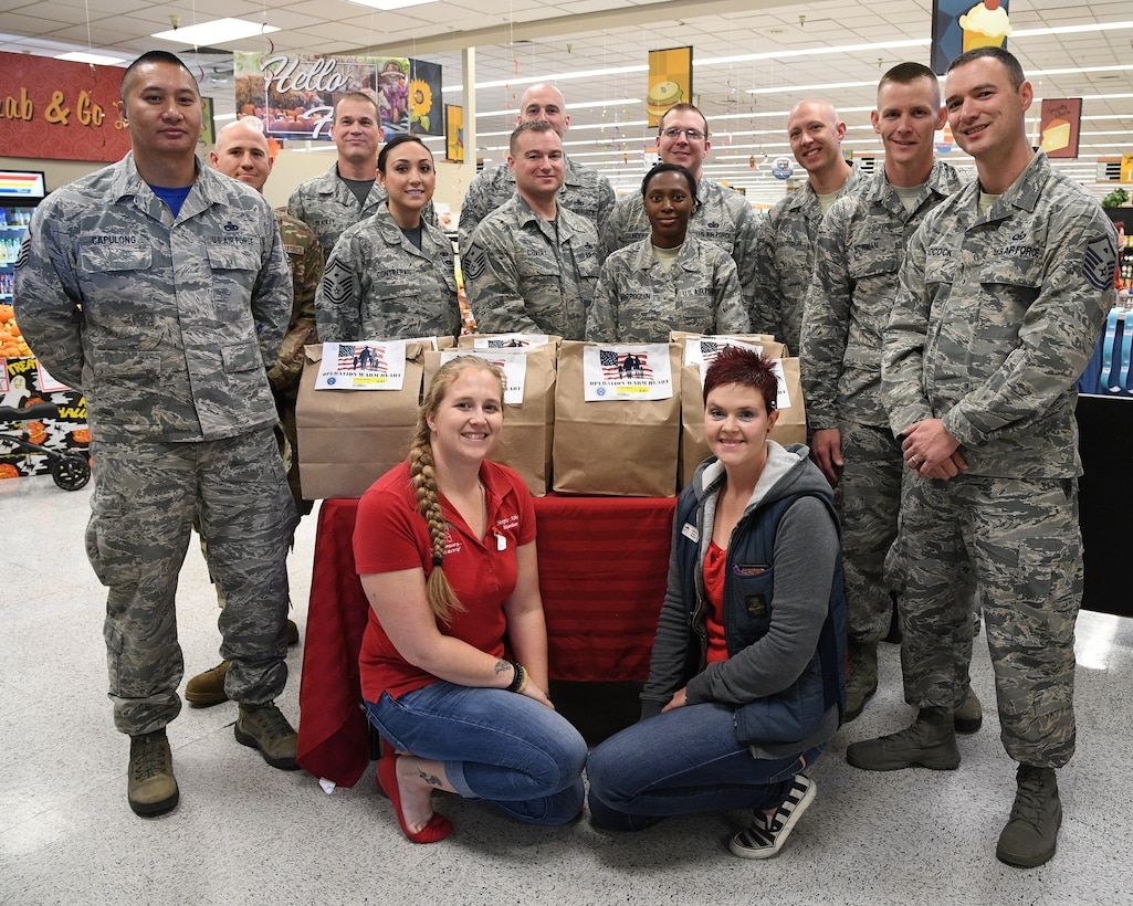 Stephanie Abbey, left, Shannon Loftus and members of Hill's First Sergeant Council pose for a group photo around a table of Operation Warm Heart Thanksgiving bags on Nov. 2, 2108, at Hill Air Force Base, Utah. The First Sergeant Council and the commissary packaged 200 bags of Thanksgiving side dishes to be sold at cost to benefit Airmen during the upcoming holiday. Commissary patrons purchase the bags which are then delivered to Airmen along wth a turkey, potatoes and a pie that were donated by commissary vendors. (U.S. Air Force photo by R. Nial Bradshaw)