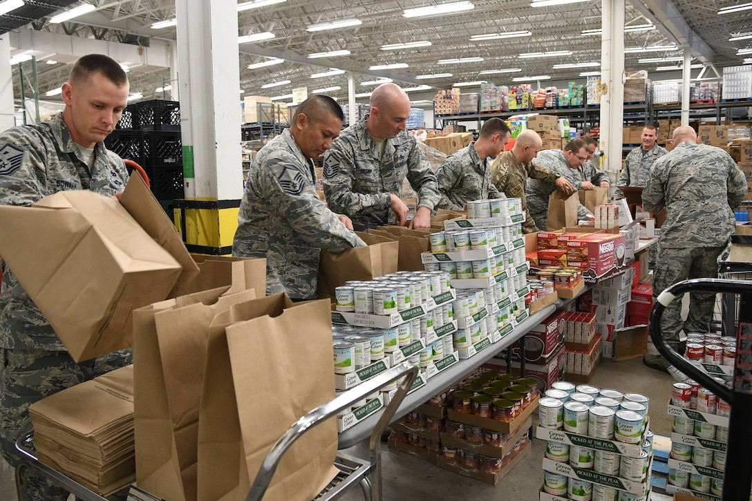 Members of Hill's First Sergeant Council pack Operation Warm Heart Thanksgiving bags on Nov. 2 at Hill Air Force Base, Utah. The bags of sides dishes along with a turkey and a pie donated by commissary vendors will be delivered to selected Airmen to assist with the upcoming holiday. (U.S. Air Force photo by R. Nial Bradshaw)