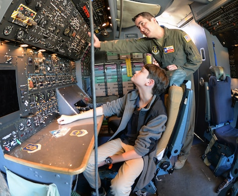 Lt. Col. Ryan A. Clark, 356th Airlift Squadron flight instructor, explains functions of the flight engineer station to Kenneth Dilanian III Nov. 2, 2018, at Joint Base San Antonio-Lackland, Texas.